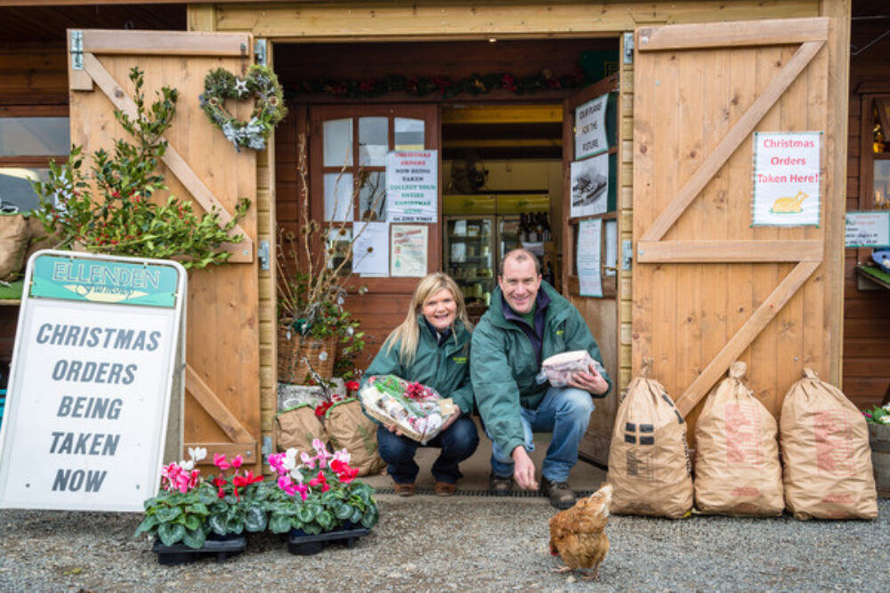 Front of timber farm shop with owners feeding chicken