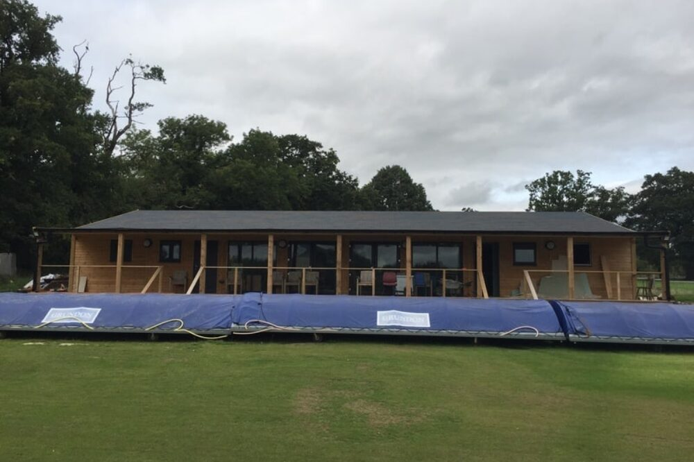 Cricket pitch with wooden clubhouse