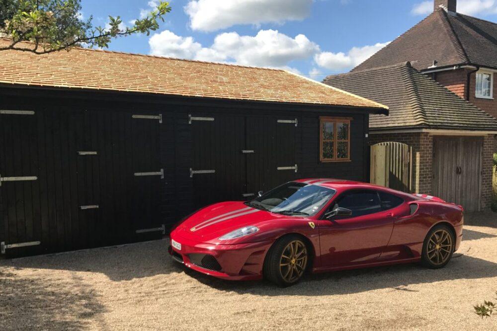 Double door black garage behind red ferrari