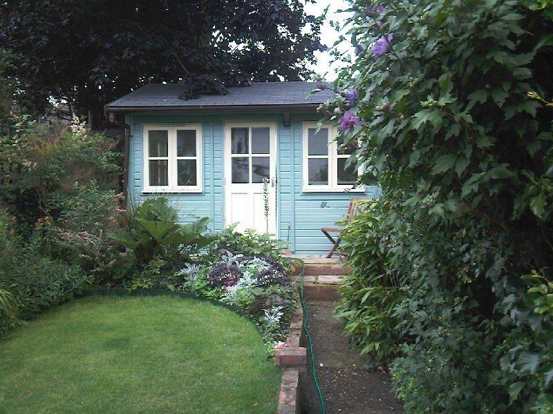 blue painted wooden garden studio building