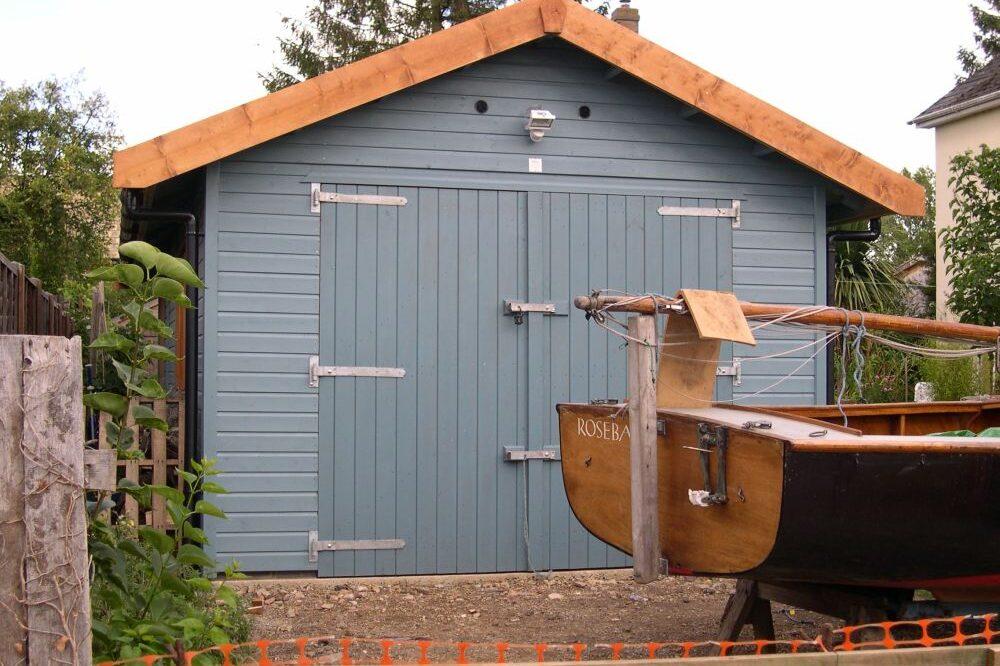 blue single garage with wooden trim
