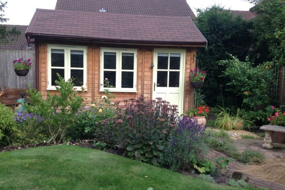 Traditional small garden room with white door and windows